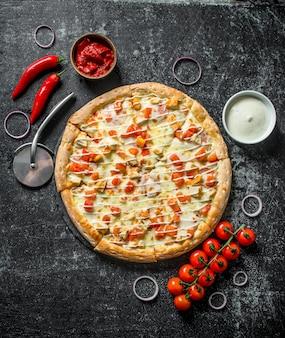 Geschnittene pizza mit kirschtomaten, zwiebelringen und käsesauce in der schüssel auf dunklem rustikalem tisch.