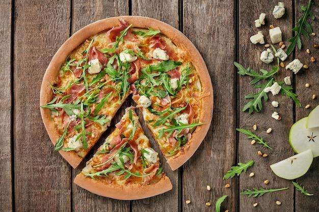 Geschnittene pizza mit prosciutto gorgonzola birne pinienkerne rucola