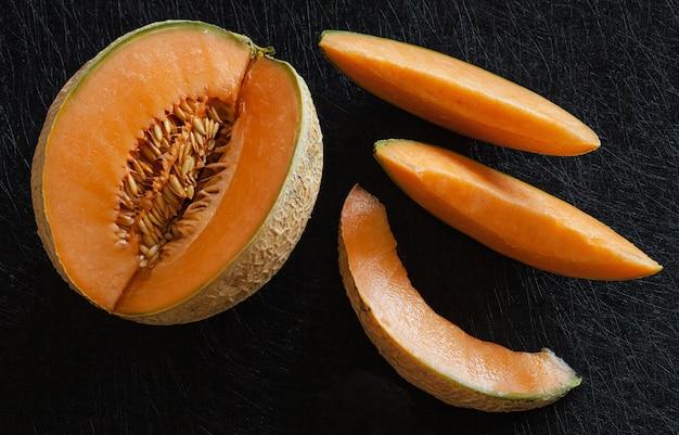 Geschnittene reife melone auf schwarzem hintergrund