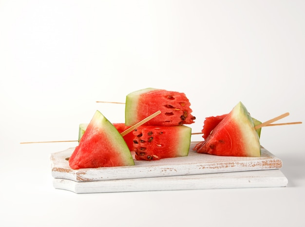 Geschnittene reife rote wassermelone mit samen auf einem hölzernen weißen schneidebrett