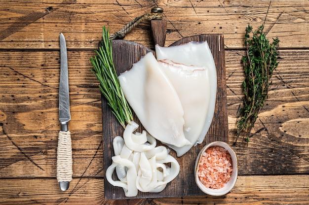 Geschnittene ringe roher calamari oder tintenfisch auf einem holzbrett mit rosmarin