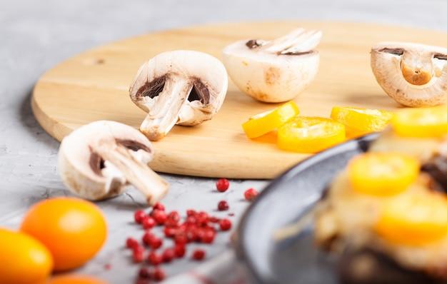 Geschnittene rohe champignons mit japanischen orangen auf grau