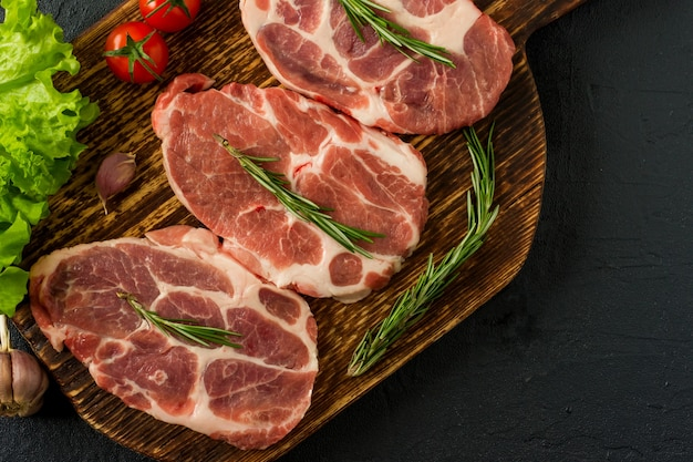 Geschnittene rohe fleischstücke zum grillen auf holzoberfläche, menükochrezepte. essen, rohes steak, rindersteak bbq, tomaten, paprika, gewürze zum kochen von fleisch