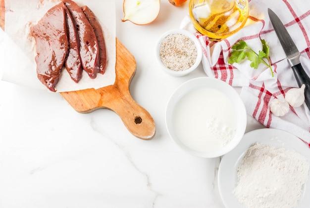 Geschnittene rohe rindfleischleber mit gewürzen, kräutern, milch und mehl, weiße marmortischplatteansicht