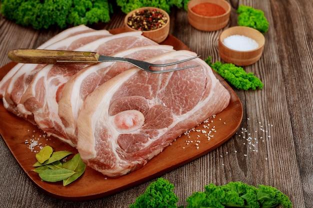 Geschnittene rohe schweineschulter mit gewürzen und gabel auf holzbrett