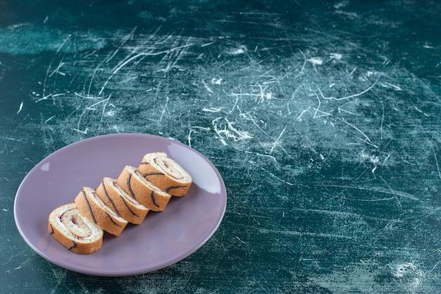 Geschnittene rollkuchen auf einem teller auf blauem hintergrund. foto in hoher qualität