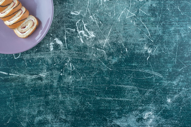 Geschnittene rollkuchen auf einem teller auf dem blauen tisch.