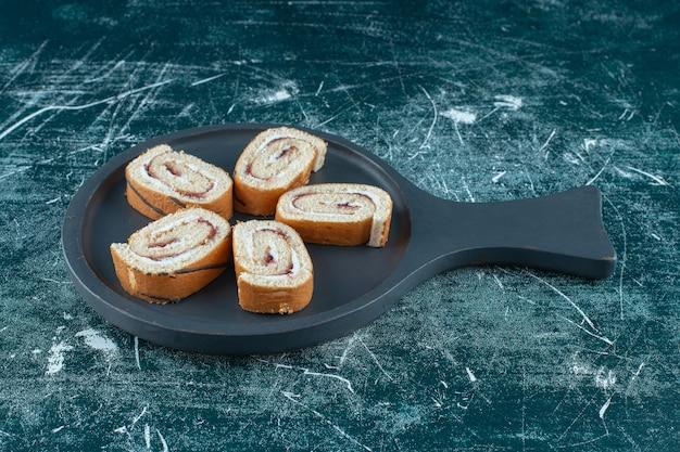 Geschnittene rollkuchen auf einer pfanne auf blauem hintergrund. foto in hoher qualität