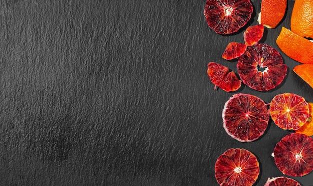 Geschnittene rot-orange scheiben auf einer schwarzen steinoberfläche