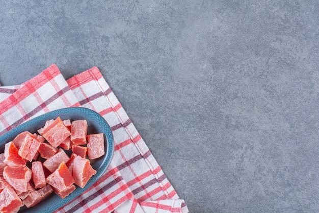 Geschnittene rote marmelade in einem teller auf geschirrtuch, auf der marmoroberfläche