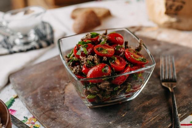 Geschnittene rote tomaten zusammen mit braunem bohnengrün auf rustikalem schreibtisch aus braunem holz