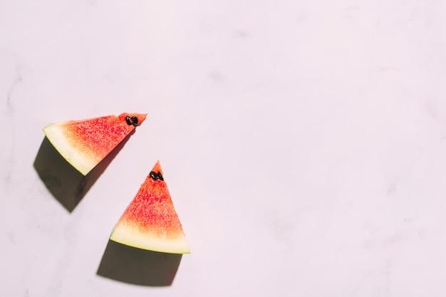 Geschnittene rote wassermelone auf rosa oberfläche