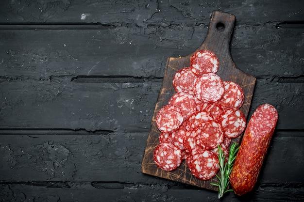 Geschnittene salami auf dem brett. auf schwarzem rustikalem tisch.