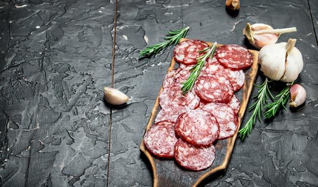 Geschnittene salami mit aromatischen gewürzen und kräutern. auf schwarzem rustikalem tisch.