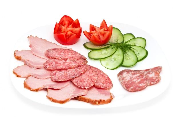 Geschnittene salami und schinken mit gurke und tomaten auf einer platte lokalisiert auf einem weißen hintergrund