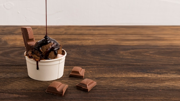 Geschnittene schokolade und eiscreme mit sirup in der weißen schüssel