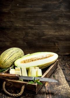 Geschnittene stücke der reifen melone auf einem alten tablett auf einem hölzernen hintergrund
