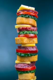 Geschnittene stücke wurst, salami, käse, gurke und tomate. fast food. zutaten für pizza. kalorien und ernährung