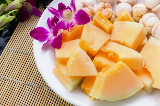 Geschnittene sunlady melone und mangostine auf weißer platte