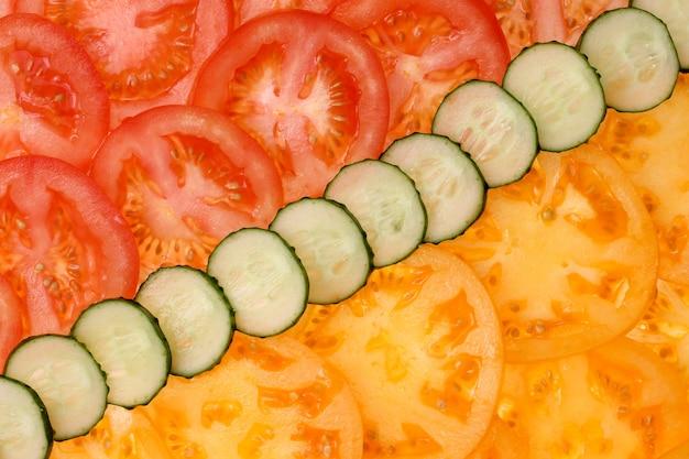 Geschnittene tomaten- und gurkennahaufnahme als hintergrund. gemüse, richtige ernährung, diät