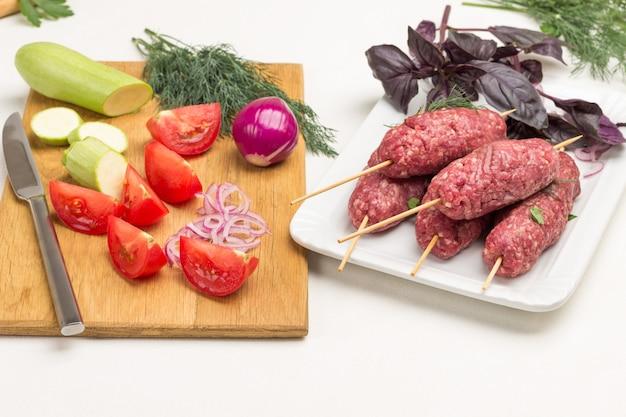 Geschnittene tomaten und zucchini auf schneidebrett. rohes hackfleisch auf holzspießen. kebab kochen. weißer hintergrund.