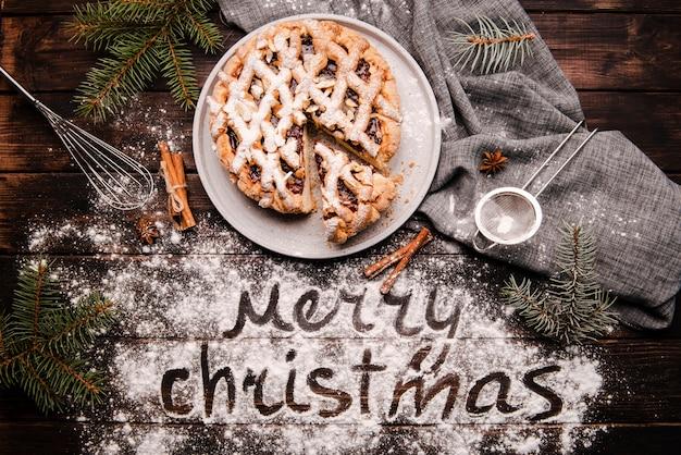 Geschnittene torte mit mitteilung der frohen weihnachten