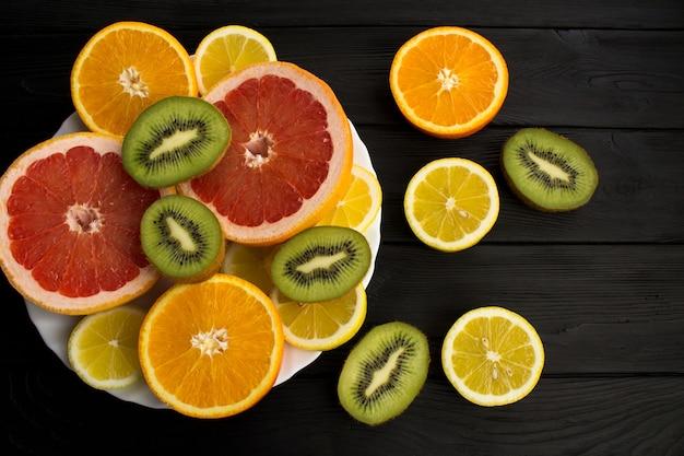 Geschnittene tropische früchte auf der weißen platte auf dem schwarzen hölzernen hintergrund. draufsicht.