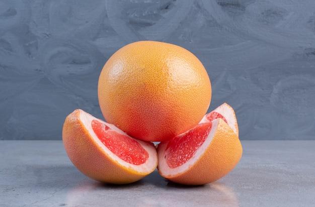 Geschnittene und ganze grapefruits auf marmorhintergrund angezeigt.