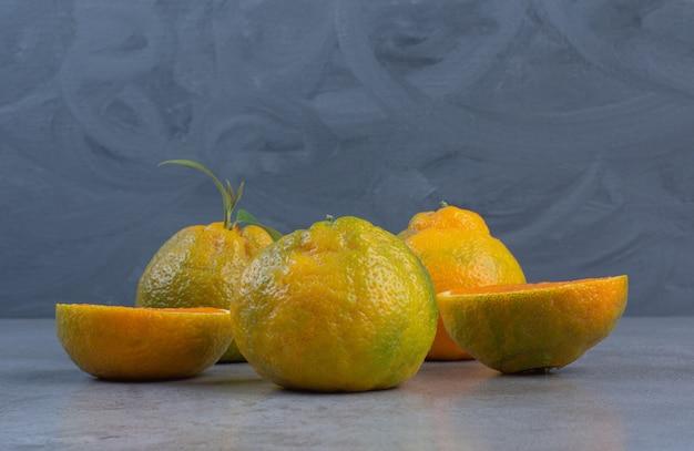 Geschnittene und ganze mandarinen auf marmorhintergrund angeordnet.