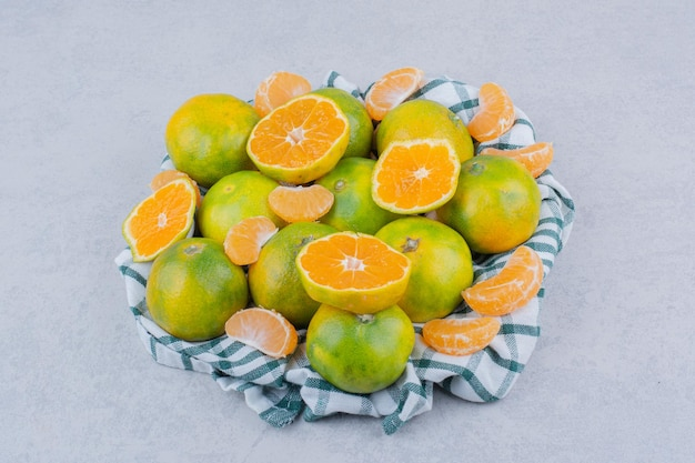 Geschnittene und ganze mandarinen in tischdecke auf weißem hintergrund. foto in hoher qualität