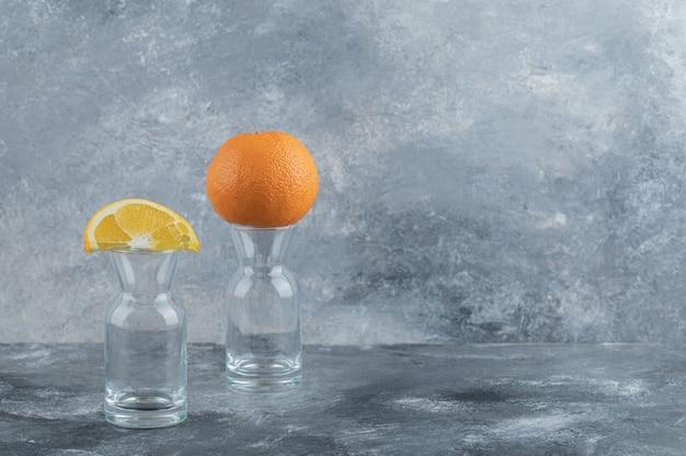 Geschnittene und ganze orange auf leeres glas.