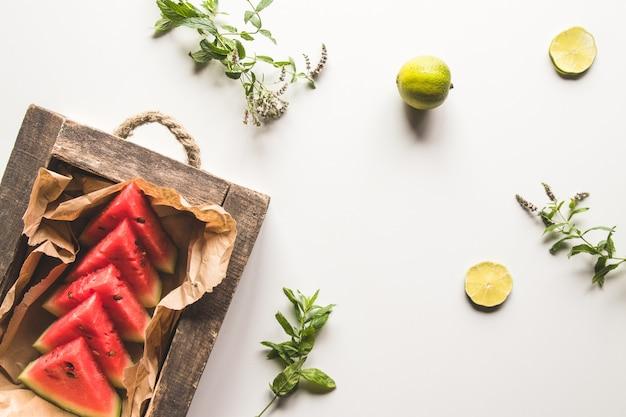 Geschnittene wassermelone mit minze und limette auf weißem hintergrund. frisches essen. gesundes gesundes essen