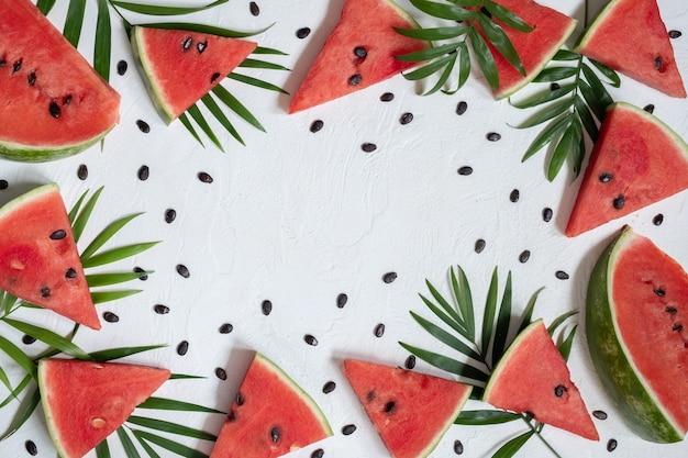 Geschnittene wassermelone mit palme auf weißem hintergrund