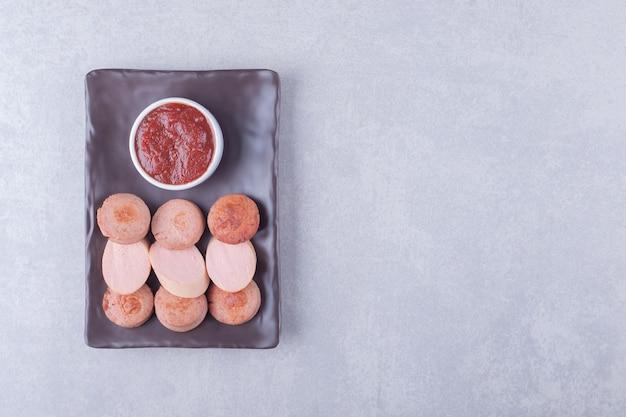 Geschnittene würstchen mit ketchup auf dunklem teller.