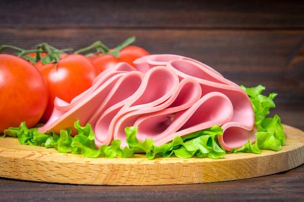Geschnittene wurst mit salat auf einem runden holzbrett.