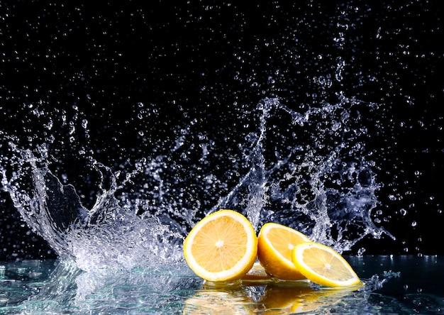 Geschnittene zitrone im wasser auf schwarzer oberfläche