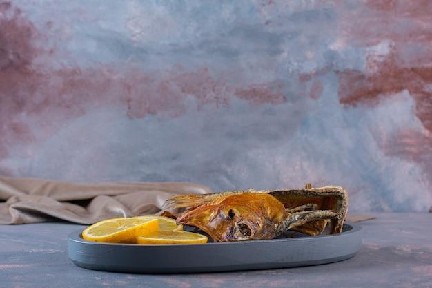 Geschnittene zitronen und getrockneter gesalzener fisch auf einem holzteller auf der marmoroberfläche