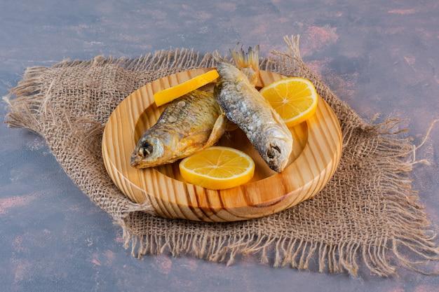 Geschnittene zitronen und getrockneter gesalzener fisch auf einem holzteller auf einer leinenserviette, auf dem marmorhintergrund.