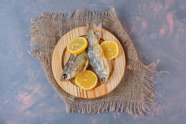 Geschnittene zitronen und getrockneter gesalzener fisch auf einem holzteller auf einer leinenserviette auf der marmoroberfläche