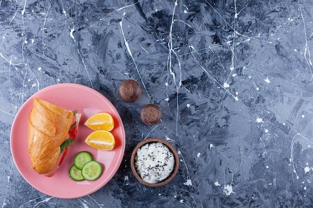 Geschnittene zitronen und gurken, sandwich auf teller neben einer schüssel käse auf blau.