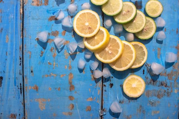 Geschnittene zitronen und limetten mit eiswürfel über blauem holztischhintergrund