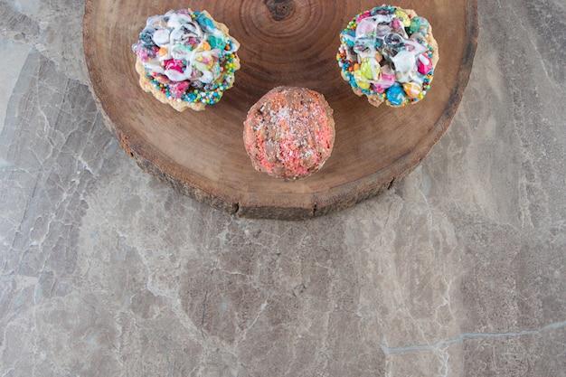 Geschnittene zitronen und minikuchen auf einem brett auf marmor.
