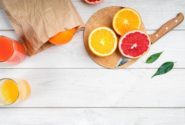 Geschnittene zitrusfrüchte auf einem holztisch, orange und grapefruit.
