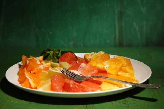 Geschnittene zitrusfrüchte auf teller, auf holztisch