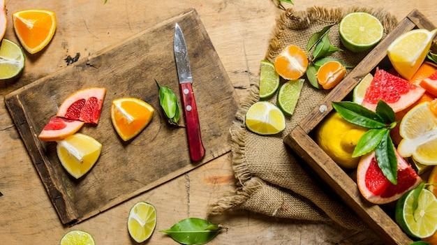 Geschnittene zitrusfrüchte - grapefruit, orange, mandarine, zitrone, limette auf dem alten brett mit schachtel