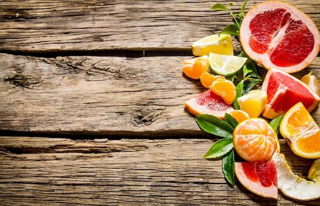 Geschnittene zitrusfrüchte - grapefruit, orange, mandarine, zitrone, limette mit blättern auf holztisch.