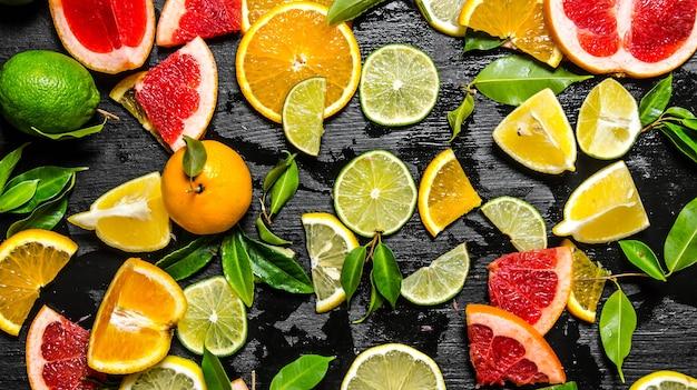 Geschnittene zitrusfrüchte. grapefruit, orange, mandarine, zitrone, limette mit blättern auf schwarzem holztisch. draufsicht