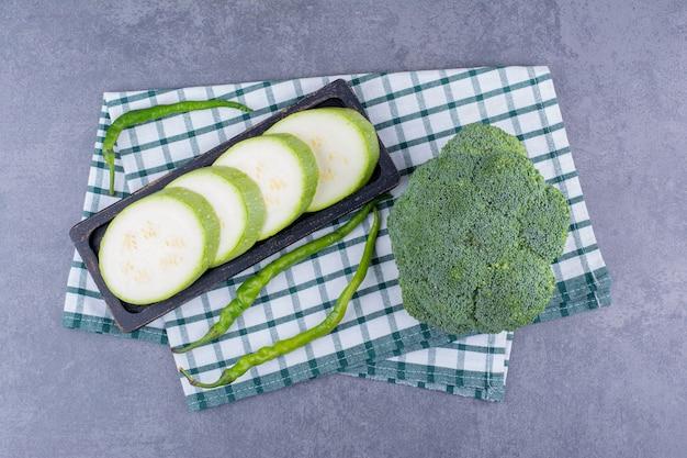 Geschnittene zucchini, grüne chilis und brokkoli auf einem karierten handtuch.