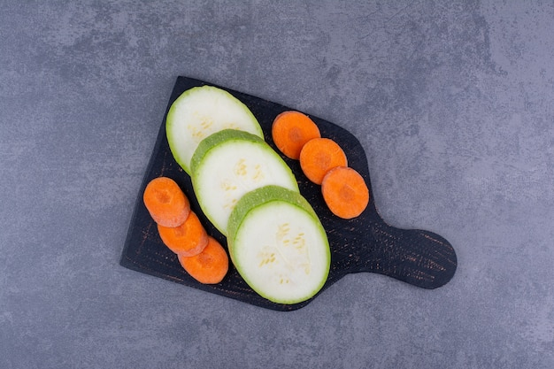 Geschnittene zucchini und karotten auf einer schwarzen platte.