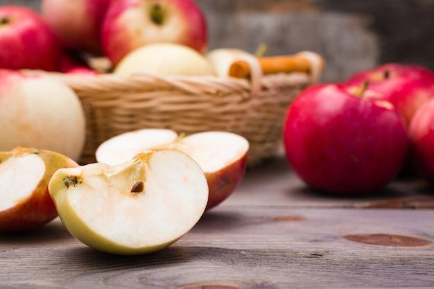 Geschnittener apfel und reife rote äpfel auf einem holztisch und in einem korb.